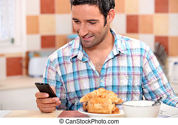 Man eating croissant and texting