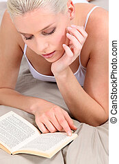 Woman reading on her bed