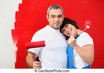 Couple painting wall red