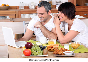 Couple looking at a laptop during breakfast