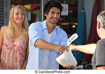 Young couple making purchases at the market