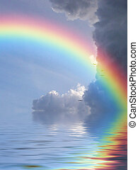 rainbow reflection - Rainbow reflected in ocean against a...