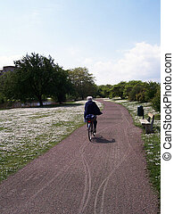 Keeping fit - An elderly lady cycling through the park