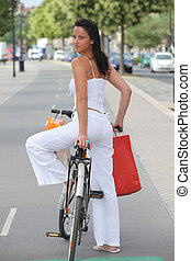Woman cycling in city with shopping bags