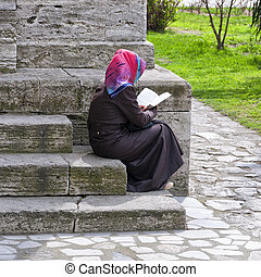 Muslim woman - A muslim woman sits on the steps outside a...