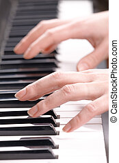Womans hands playing music on the piano