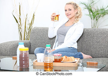 Woman having breakfast in her living room