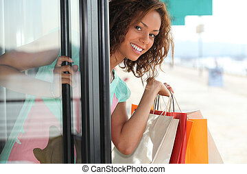 Woman with shopping bags coming out of shop