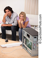 Couple sat in front of broken computer