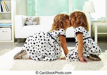 Twin girls - Portrait of happy twin girls kissing at home