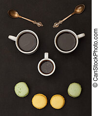 Happy face - Tree cups coffee and macaroon arranged in happy...
