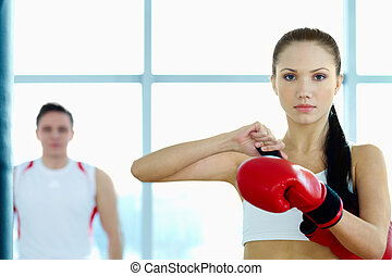 Female fighter - Portrait of young woman in red boxing...