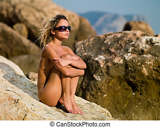Girl at Sea - naked girl sitting on the rocks