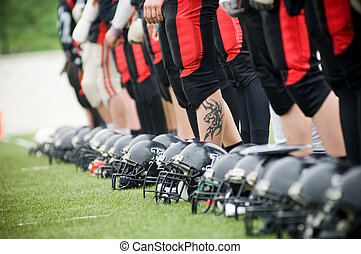 Row of football helmets and feet on grass, selective focus