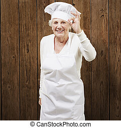 senior woman cook doing an excellent symbol against a wooden...