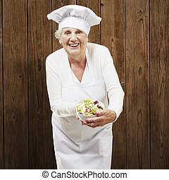 senior woman cook holding a bowl with salad against a wooden...