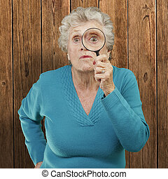 portrait of senior woman looking through a magnifying glass...