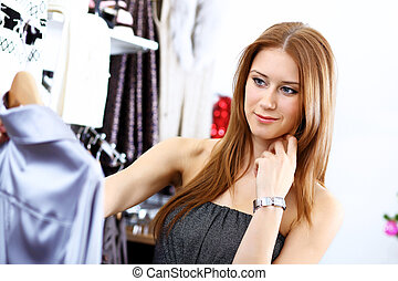 Young woman inside a store buying clothes - Portrait of...