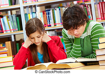 Diligent pupils - Serious boy and girl reading books at...