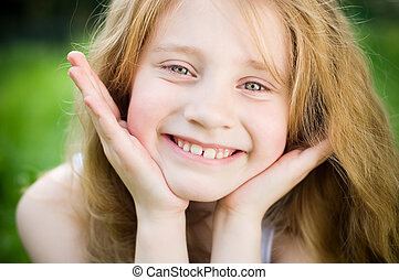Smiling little girl outside in green grass