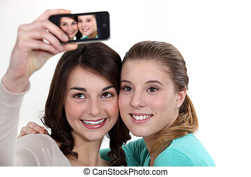 Girls taking picture with mobile phone