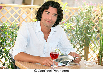 Man enjoying a glass of wine at an outdoor cafe