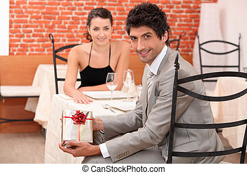 couple dining in a romantic restaurant, the man is showing a present