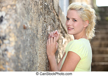 Young blond woman standing against a wall