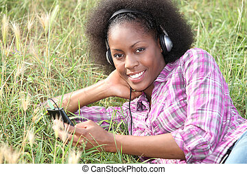 young woman lying on the grass and listening music