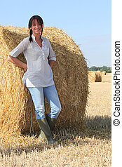 Woman in wellington boots standing in a field of hay