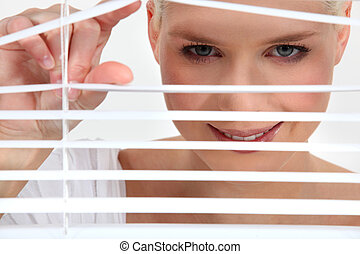 Woman peering through blinds