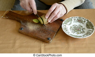 old woman hands cut up kiwi