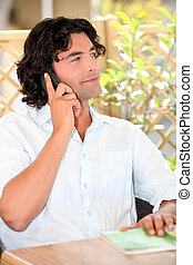 man seated outdoors making a call