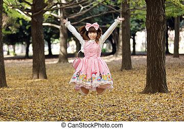 happy japanese lolita cosplay jumping in harajuku park,...