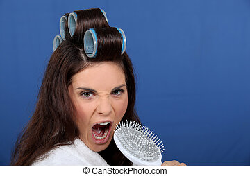 woman with curlers in her hair singing