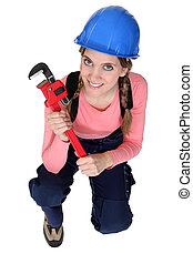 Female plumber kneeling with wrench