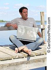 Man on laptop by a lake