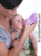 Girl giving baby her bottle