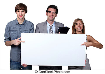 Young people pointing at blank board