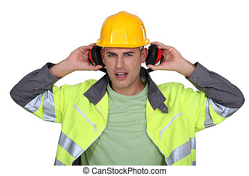builder with hard hat removing earmuffs