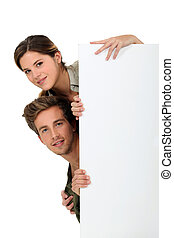 Man and woman peeking behind a white panel