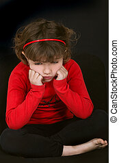little girl pouting with face resting on hands against black...