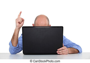 Man at a laptop pointing his finger in the air
