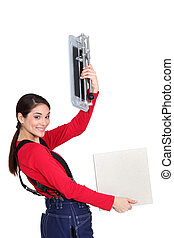 Tradeswoman holding up a tile cutting machine and a tile
