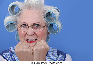 A mature lady with hair rollers.