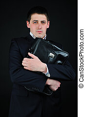 man and suitcase - Businessman in a suit holds a briefcase