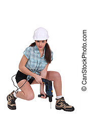 Sexy woman using a power tool