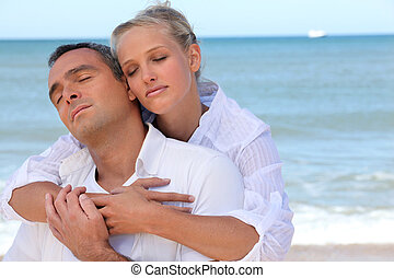 Couple standing on secluded beach