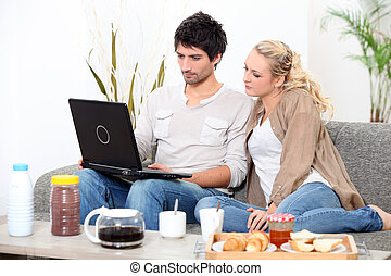 Couple using a laptop computer at breakfast
