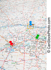 Color pushpins marking a location on a road map